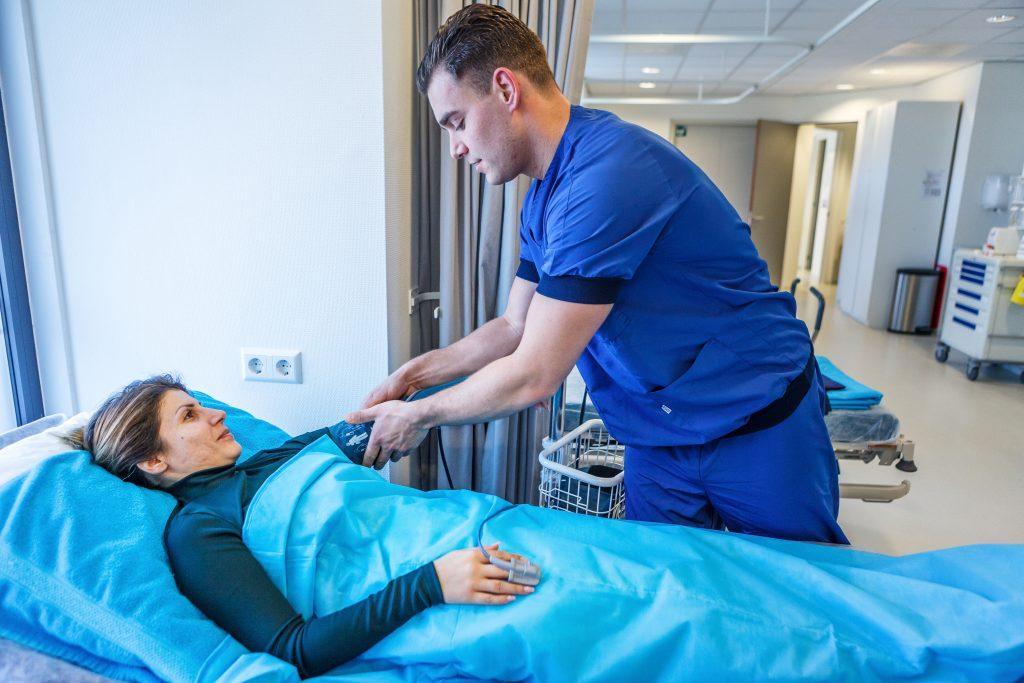 Verpleegkundige meet bloeddruk patiënt